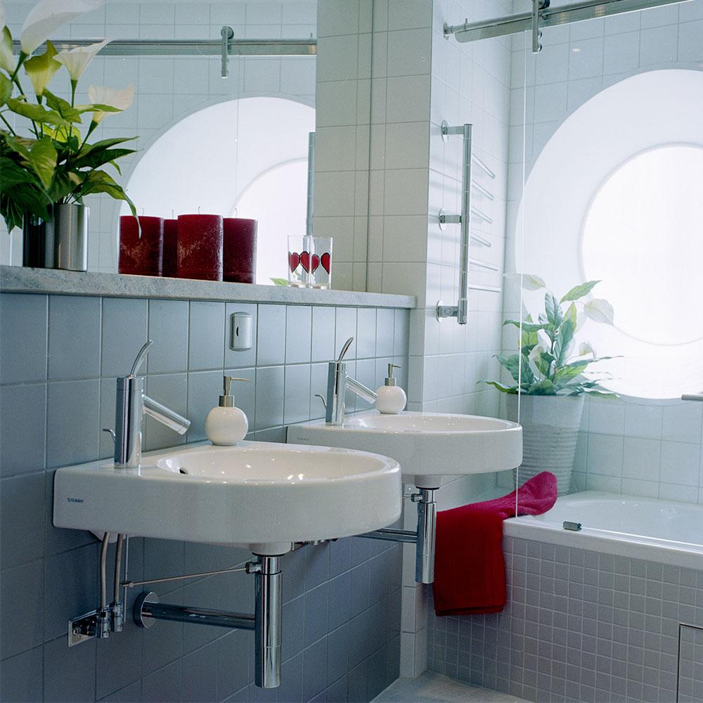 Badrum med grått kakel och stenhylla vid spegel