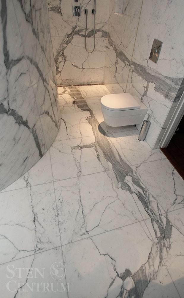 Marmorbadrum av vit marmor och grå vener med åderföljning från golv upp på vägg