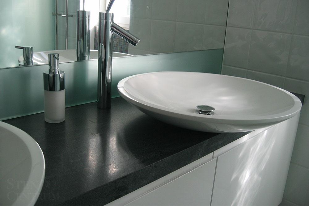 vita vaskar och svart granitbänk i badrum