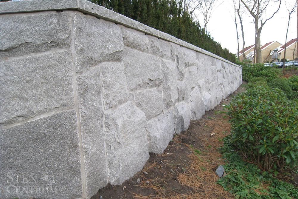 Mur i grå granit specialhuggen på plats med avtäckning i bohusgranit