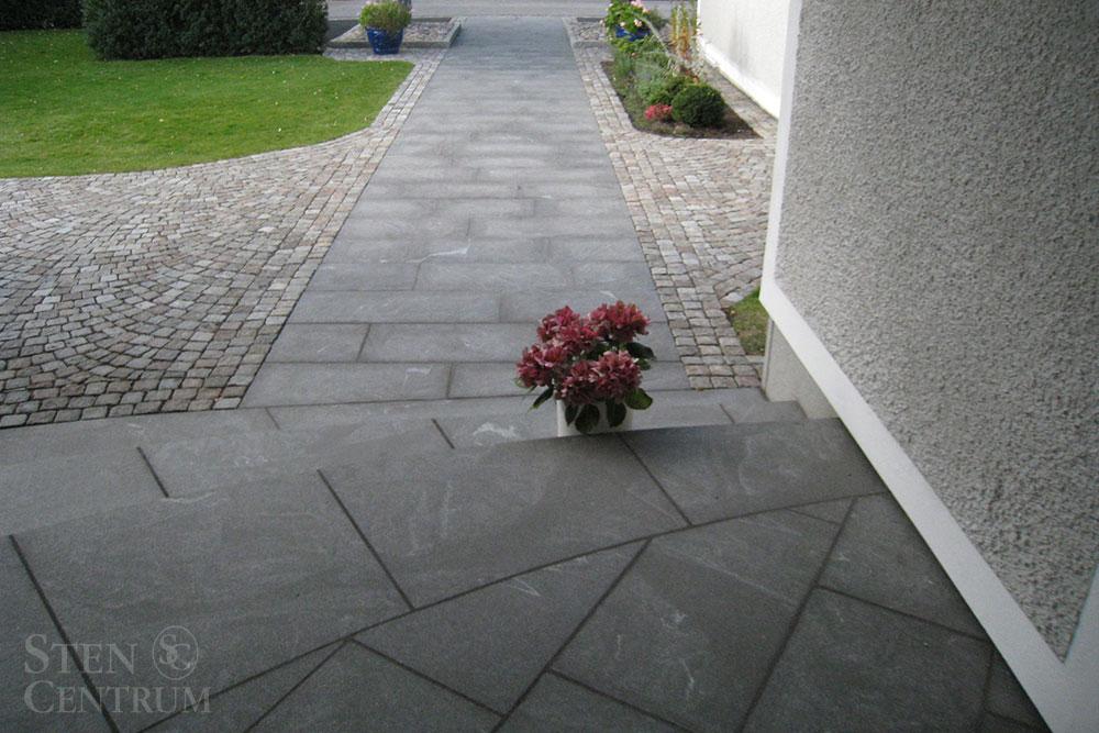 Granittrappa vid entré i mörkgrå natursten med gångar i granithällar och gatsten