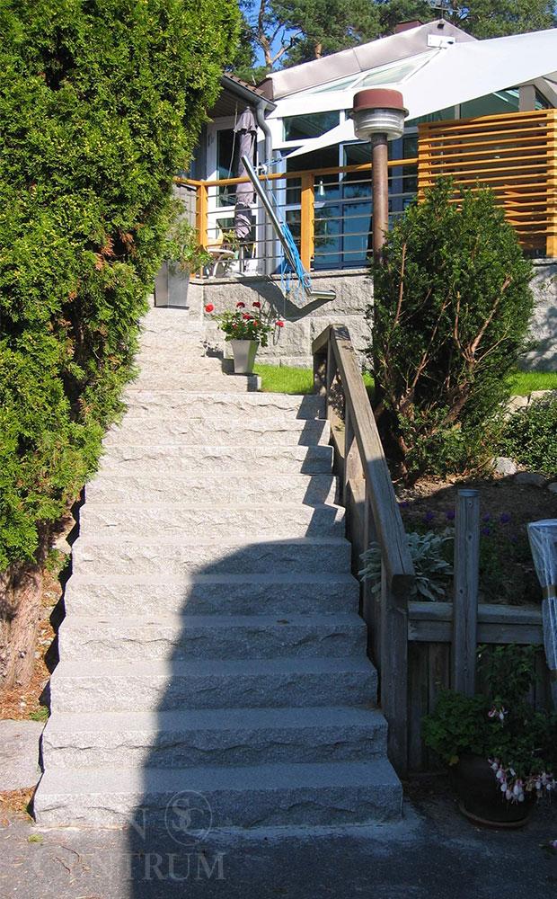 Lång granittrappa i massiva steg med flammad ovansida och huggna kanter