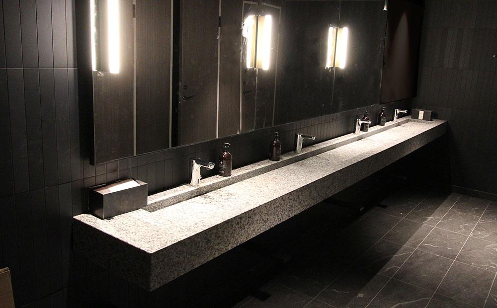 Grå granitvaskar och svart granitgolv på hotelltoalett