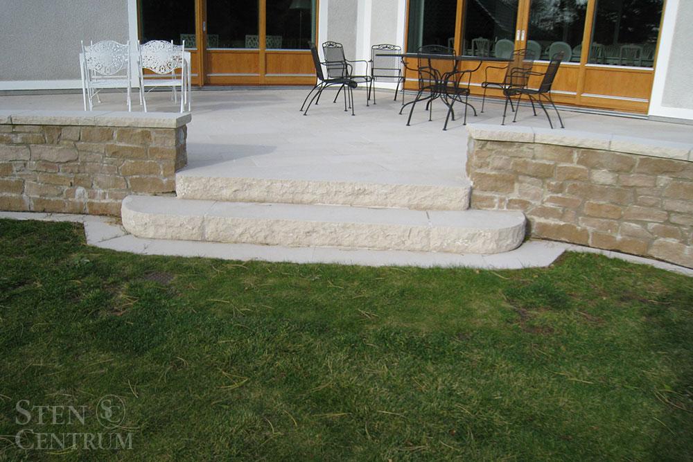 Massiv kalkstenstrappa vid altan med plattor av samma ljusa sten och mur i brun kalksten