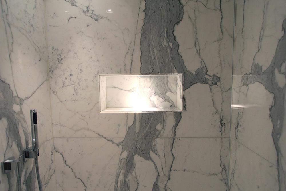 Belyst nisch i marmorbadrum med ådermönstring