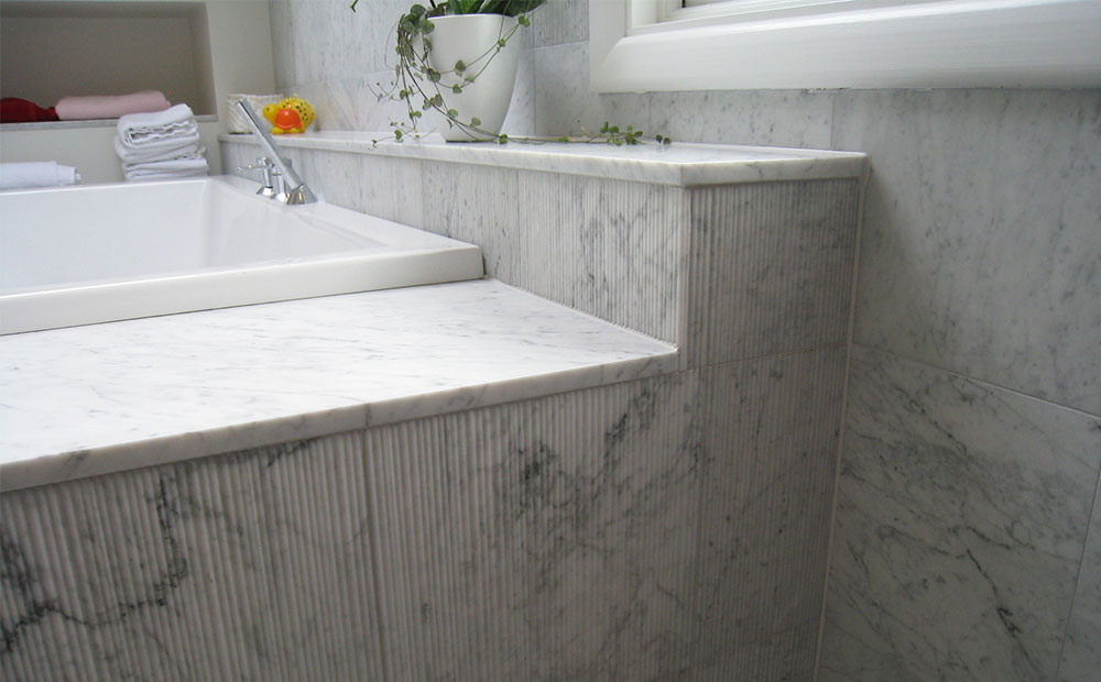 Detalj av badkar i carraramarmor med ytfinishen bamboo