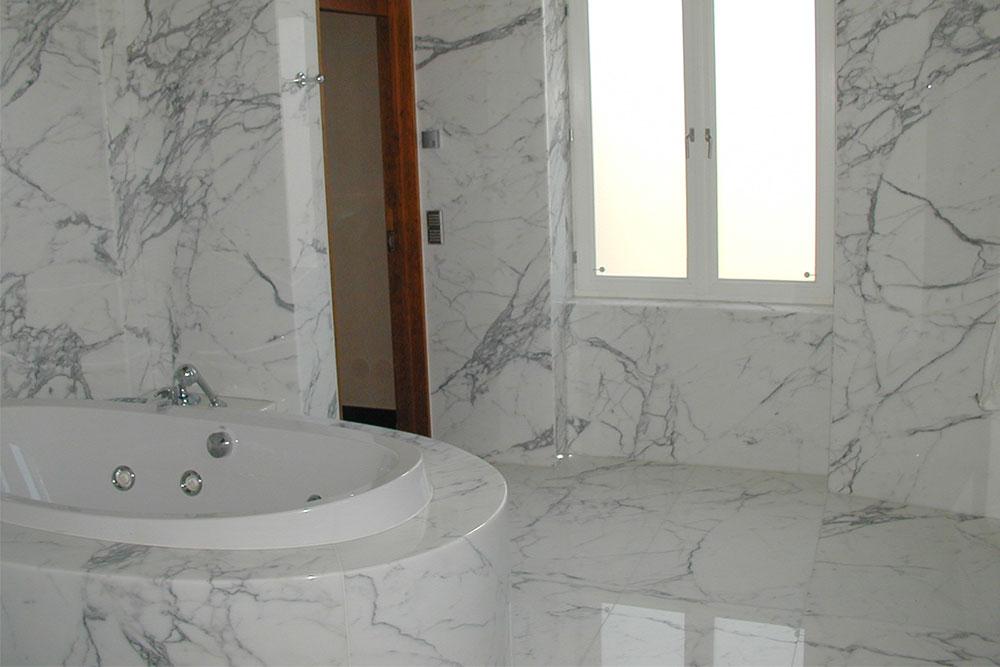 Badrum helt klätt med vit statuario-marmor samt även badkarsinklädnad