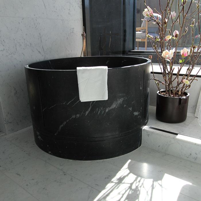 Svart runt Marmorbadkar med golv och väggar i Bianco Carrara marmor på hotell at Six