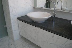 Svart granitbänkskiva med vita marmorväggar och marmorgolv i badrum