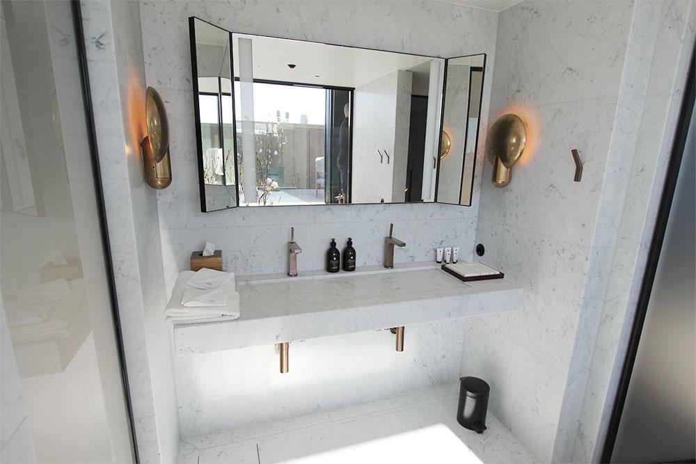 Vitt marmorbadrum i hotellsvit med specialtillverkad vask
