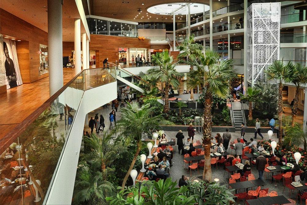 Köpcentrum med kalkstensgolv, trägolv och mycket växter