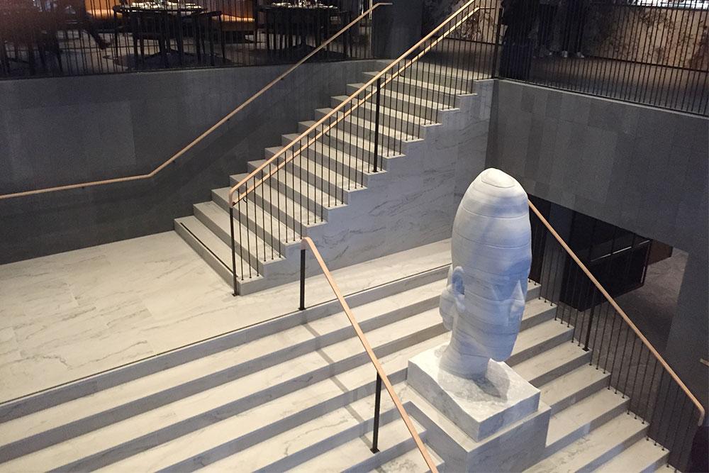 Hotelltrappa i vit kvartsit med staty i vit marmor