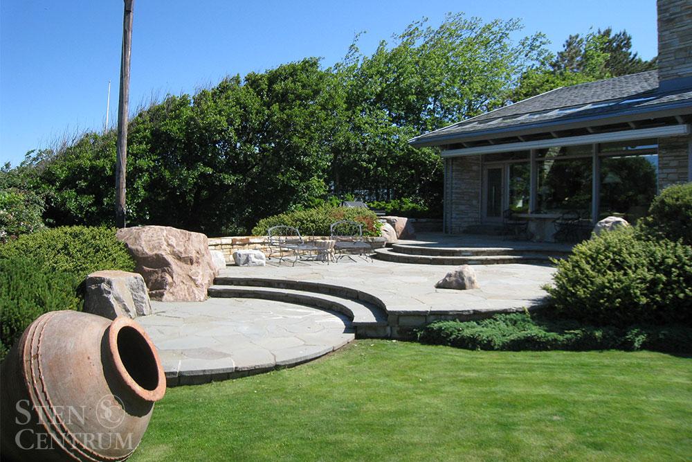 Trädgårdsmiljö med svängda terrasser i oregelbunden skiffersten