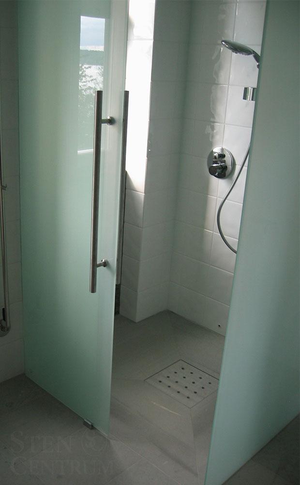 Kalkstensgolv i badrum med lock av kalksten till golvbrunn i dusch