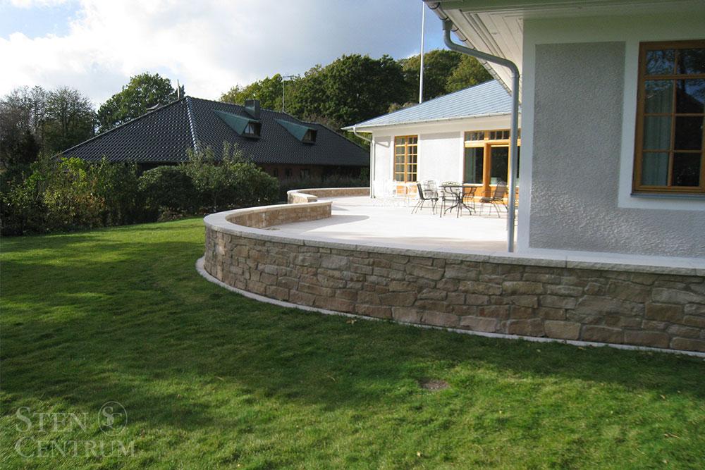 Svängd mur av brun kalksten med avtäckning och altan i beige kalksten