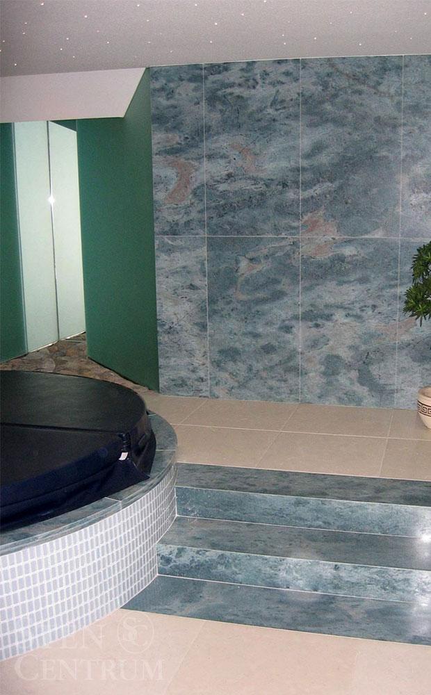 Turkos-blå natursten på vägg och som steg vid jacuzzi i badrum