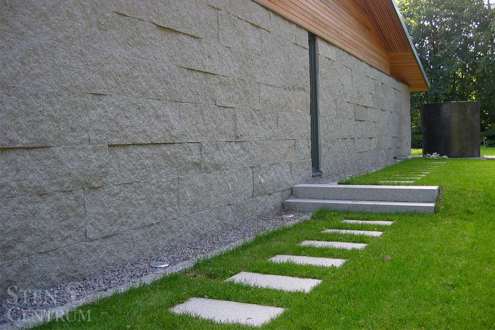 Husfasad av grå granit och trä samt granithällar som gång och massiva granitsteg