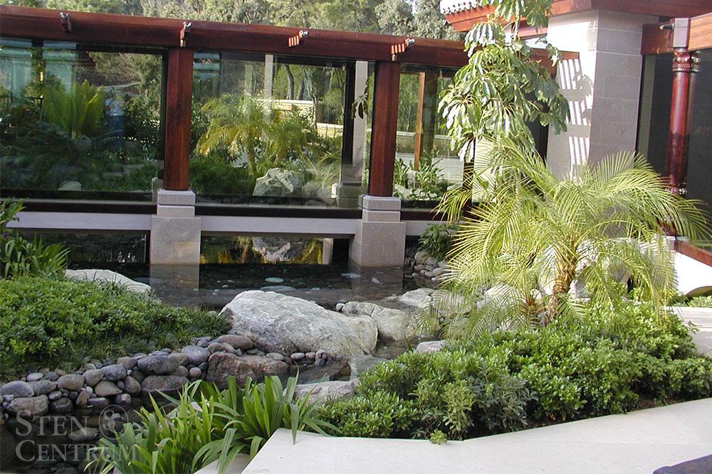 Utomhusmiljö med gröna växter, natursten och pelare samt av fasad av kalksten