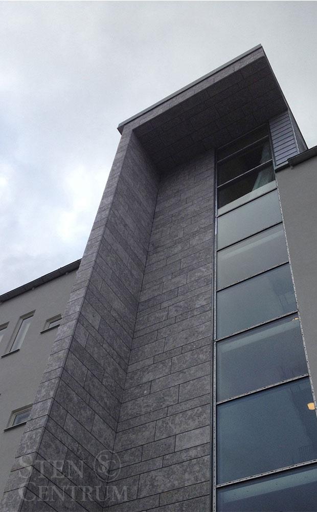 Stenplattor av flammad kalksten monterade med olika längder och bredder på fasad