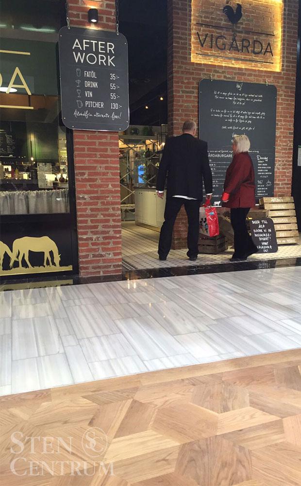 Vitt marmorgolv tillsammans med trägolv i köpcentrum