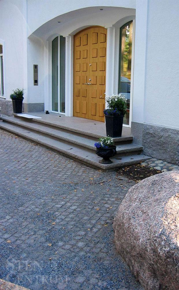 Kalkstenstrappa vid entré och gatsten på marken