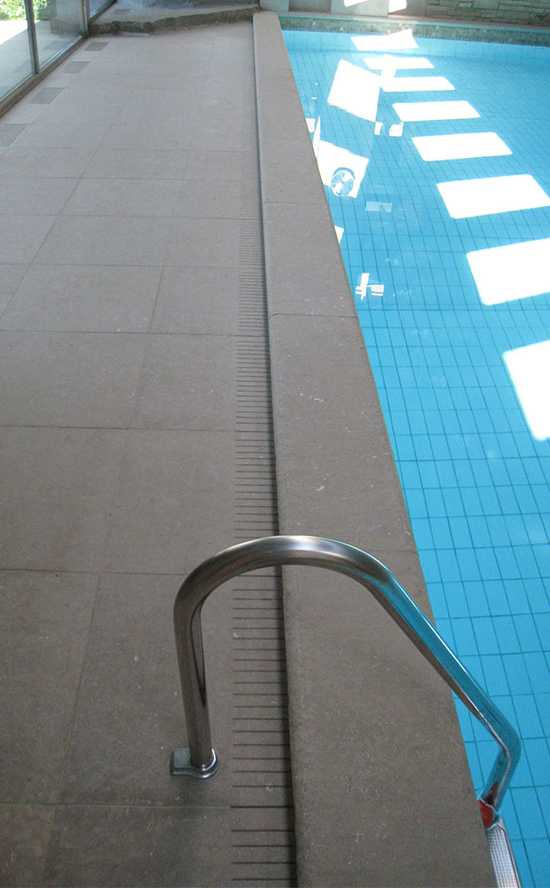 Poolkant i natursten med avrinning och golvplattor i samma material