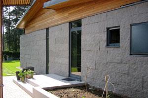 Husfasad i grå bohusgranit med kluven yta tillsammans med träfasad