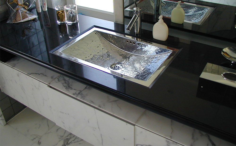 Polerad svart granitbänkskiva med förkromad vask och badrumsmöbel i vit marmor