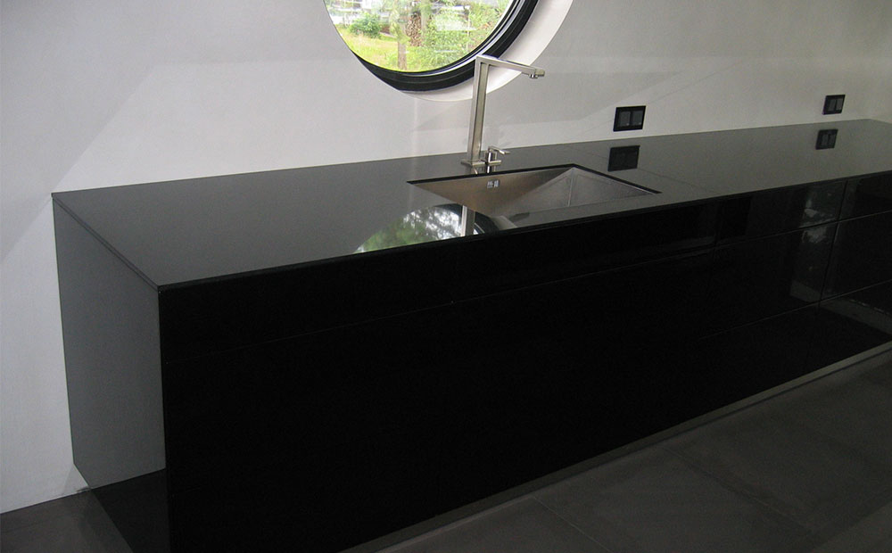 Köksbänk i högblank mörk granit med svarta köksluckor