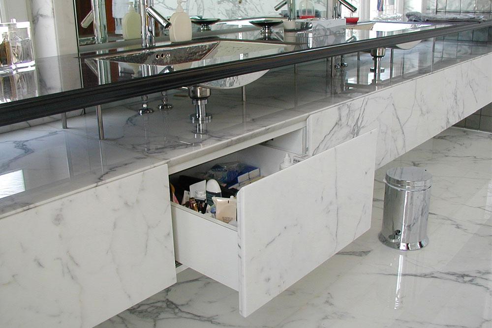Badrumsmöbel i vit statuariomarmor med granittopp som har infällda handknackade vaskar. Golv och väggar i Statuario marmor