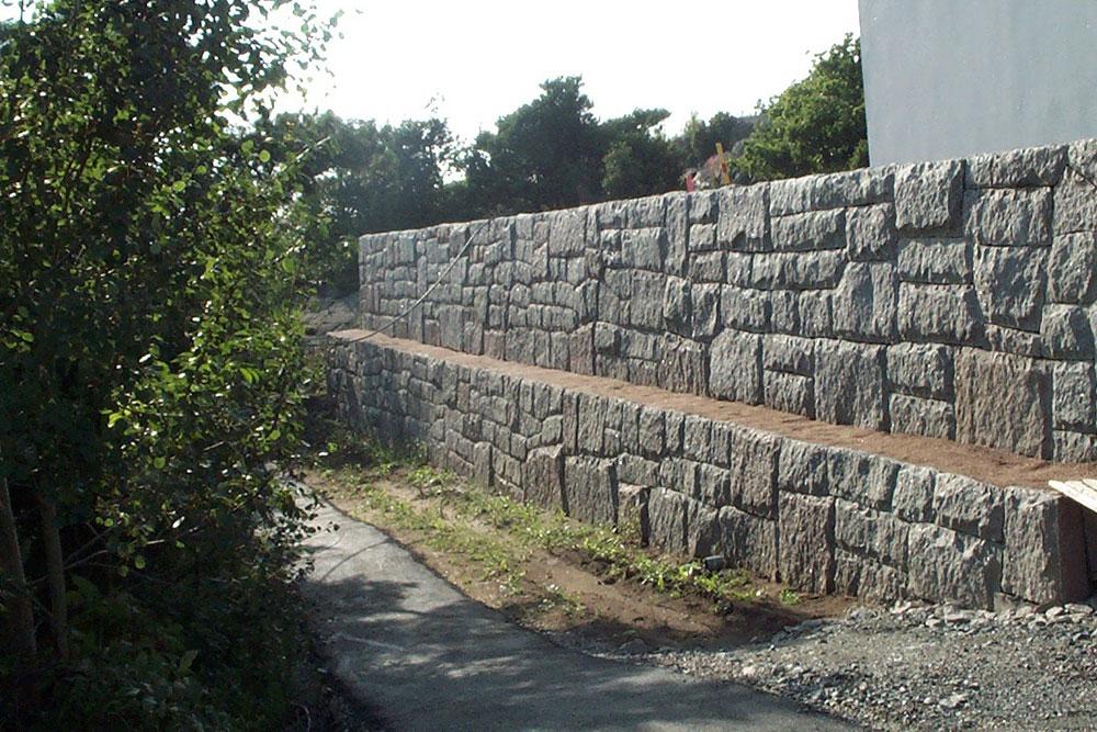Mur av svensk granit specialhuggen på plats