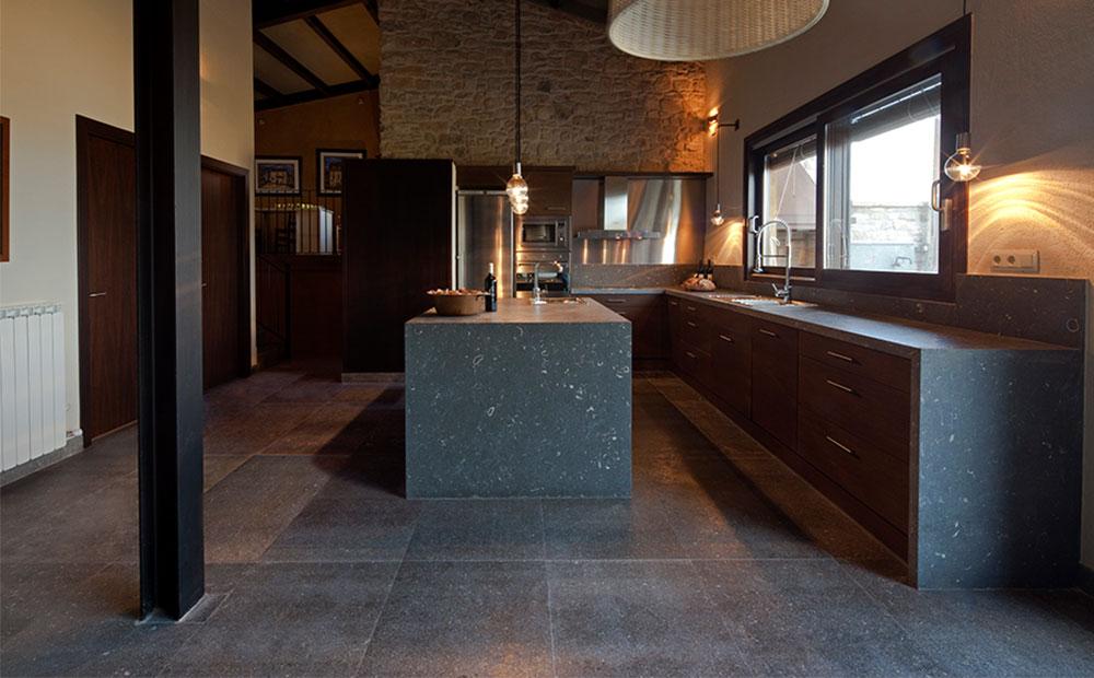 Stort kök med köksö och bänkskivor i mörk grå kalksten med fossiler. Kalkstensplattor på golv.