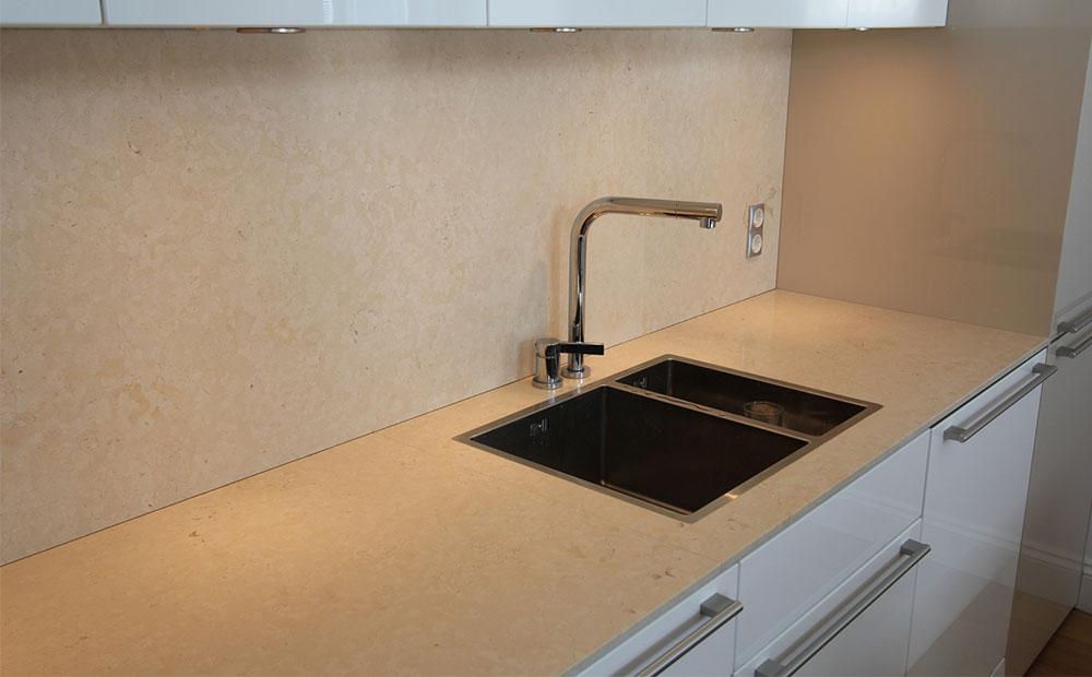 Bänkskiva och stänkskydd i beige kalksten med planmonterad Blanco vask
