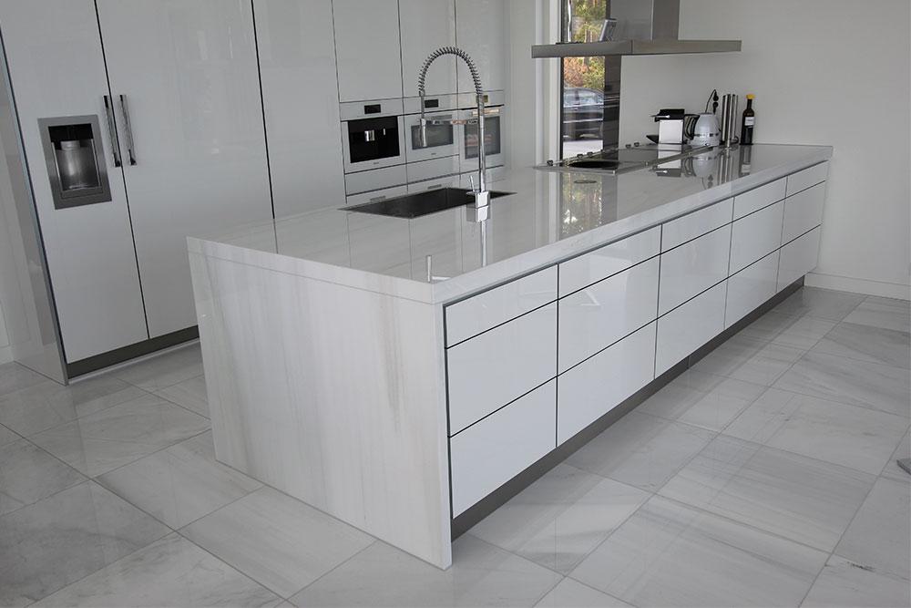 Köksö medbänkskiva och brolösning i vit marmor med golv i samma marmor