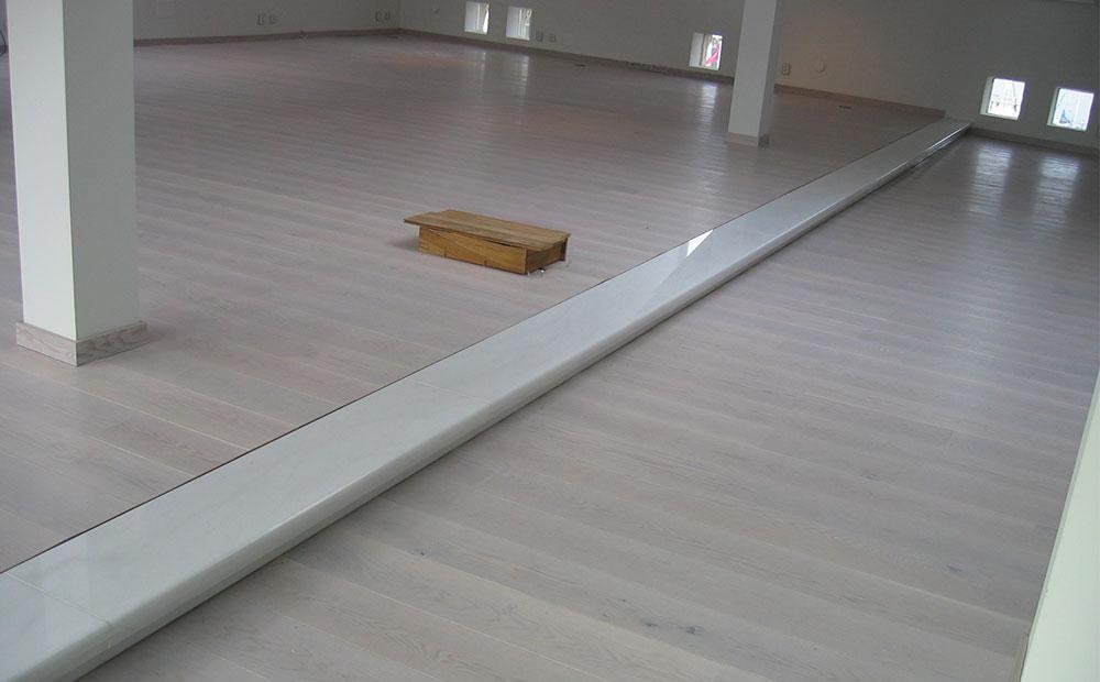 Vitt långt marmorsteg i vardagsrum med trägolv