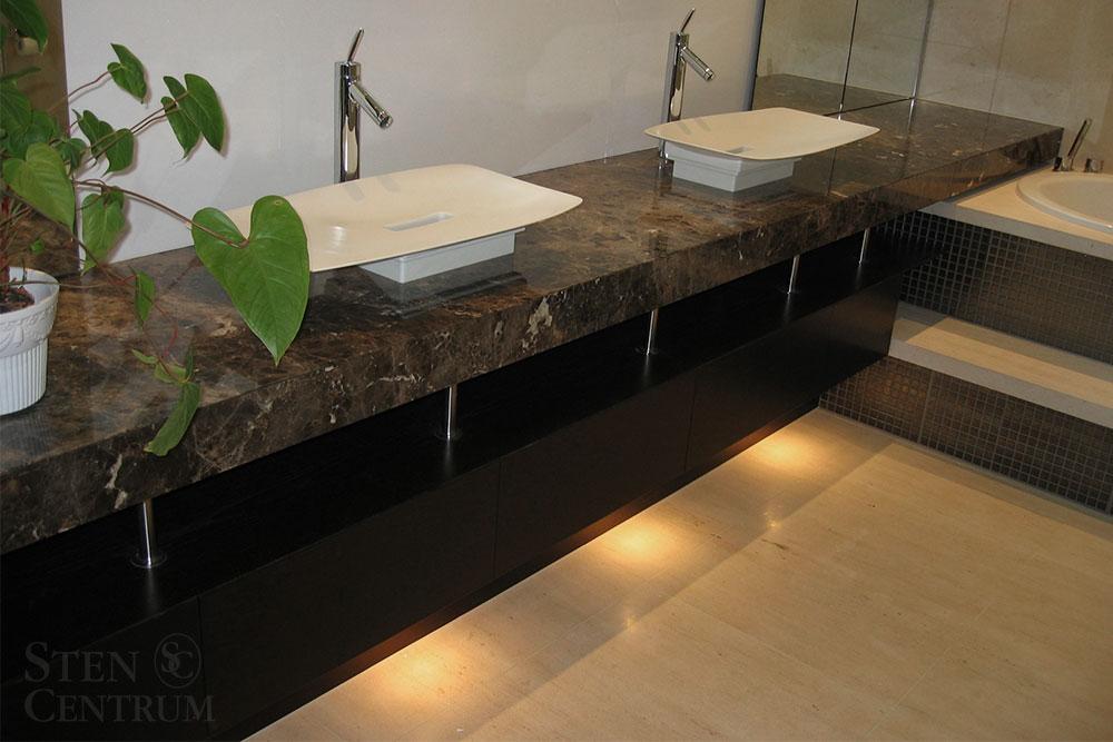 Brun marmorbänkskiva och ljust kalkstensgolv i badrum
