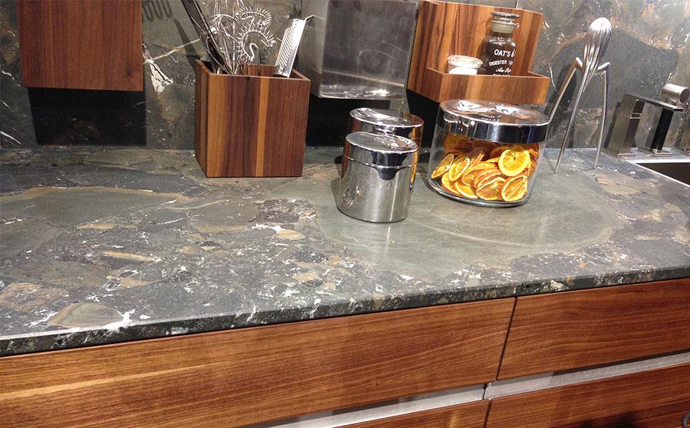 Brunmelerade stenbänkar och stänkskydd i kök med bruna träluckor