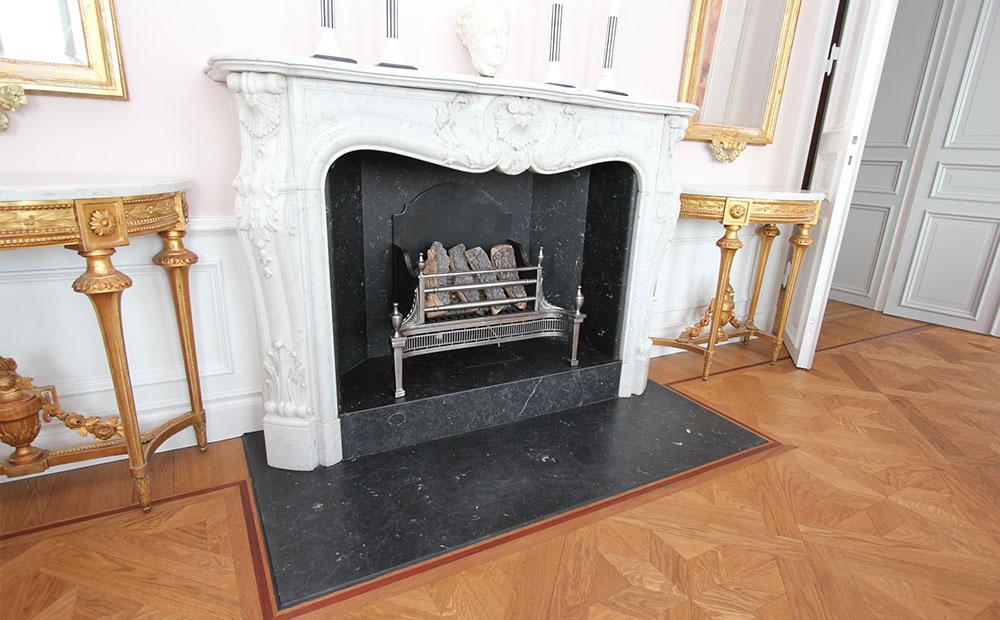 Gammaldags eldstad i ljus marmor med golv framför i svart marmor