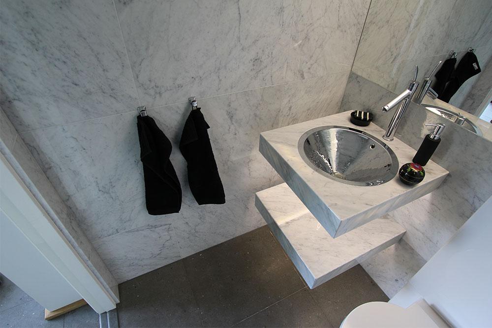 Litet badrum i Bianco Carrara marmor och kalksten med specialtillverkad badrumsmöbel och förnicklad handgjord vask från Jandelle