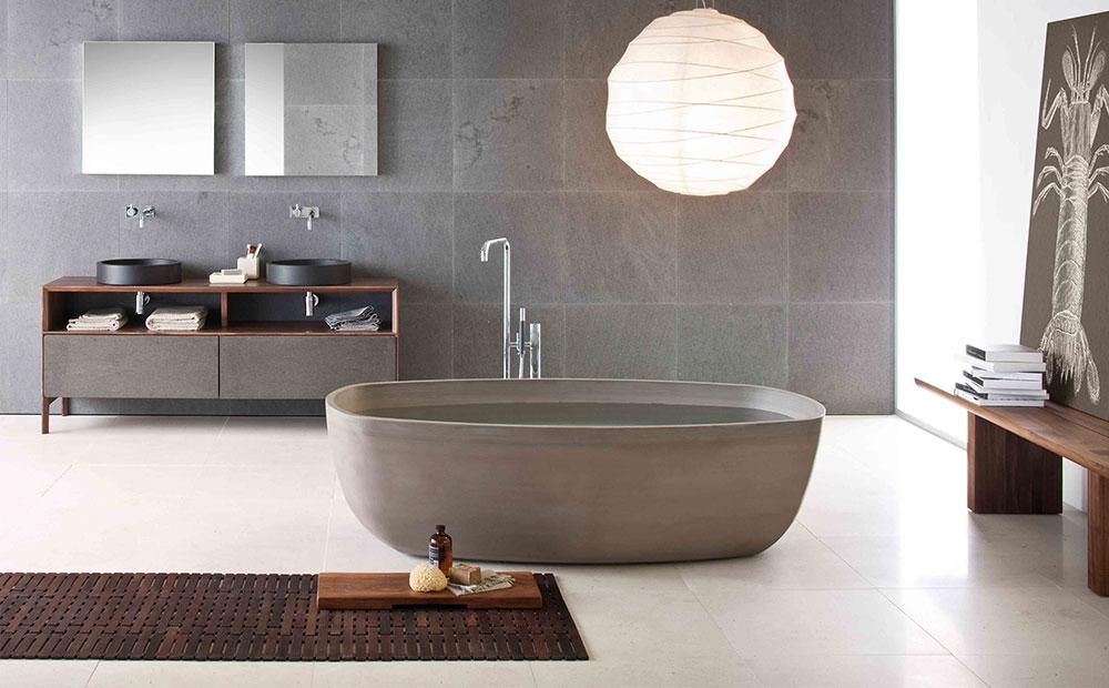 Badrum med marmorgolv grå stenväggar och badkar i massiv sten