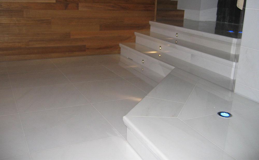 Vita marmorgolvplattor och vita marmorsteg med infrästa spottar i badrum