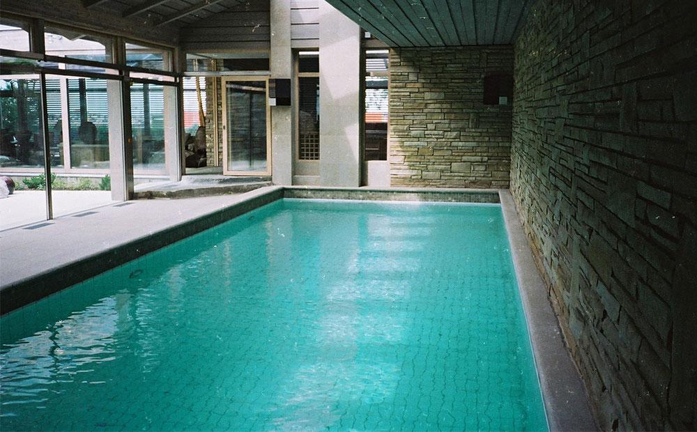 Murade kalkstensväggar vid pool i poolrum med poolavtäckning och golv av kalkstensplattor