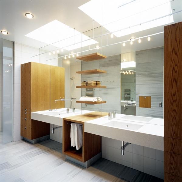 Badrum med golv och väggar i grå kalksten och badrumsmöbel av ek