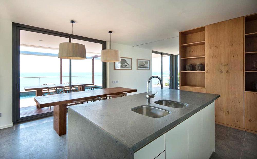 Kök med köksö och golv av grå kalksten