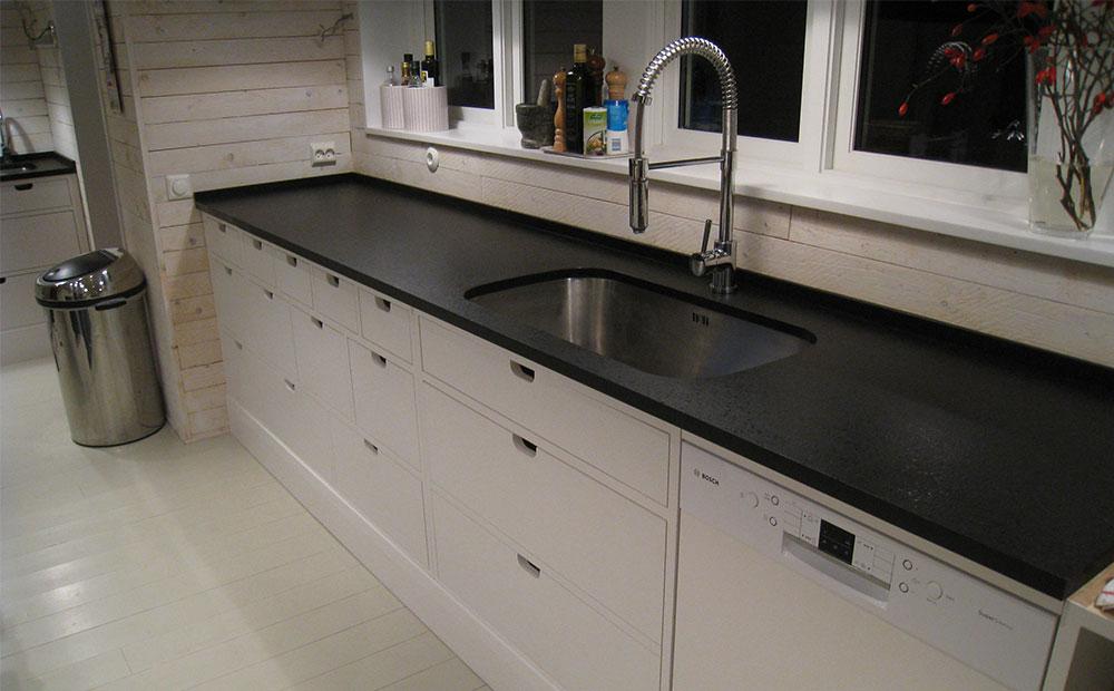 Vitt kök med kökskbänk i svart granit med flammad och slipad yta
