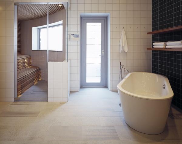 Badrumsgolv av grå kalksten med vitt badkar