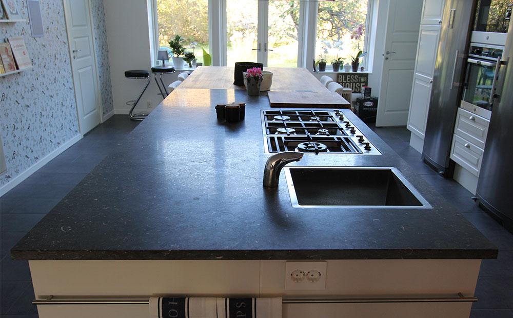 Stor köksö av mörkgrå kalksten med infälld vask och häll