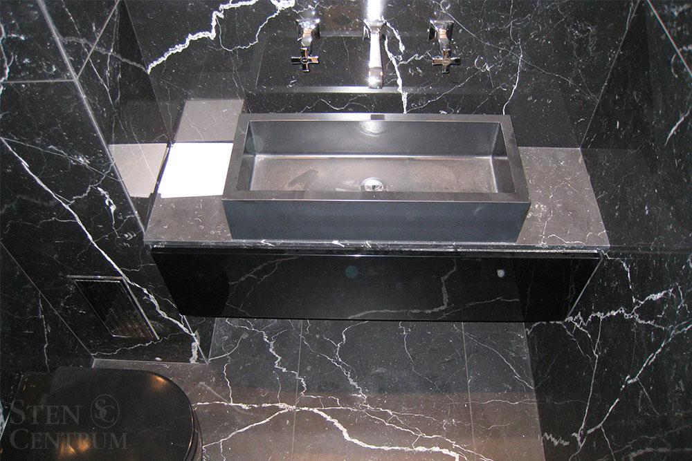 Badrumsgolv och väggar i svart marmor med svart porslin