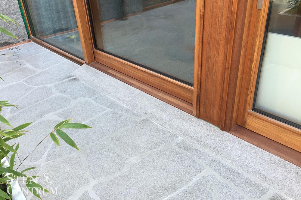 Marksten i oregelbunden bohusgranit vid dörr mot altan