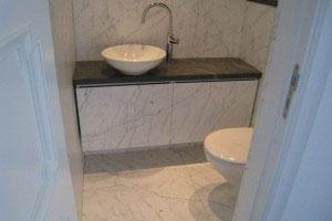 Granitbänkskiva i badrum med porslinsvask samt golv, väggar och badrumsskåp i vit marmor